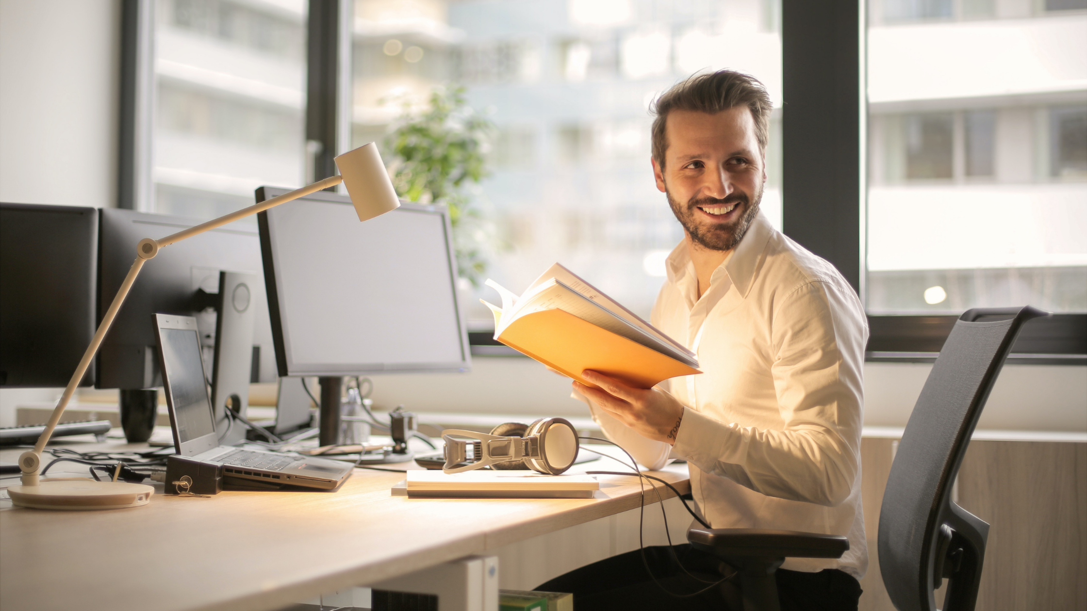 A man working at his desk who seems happy.
